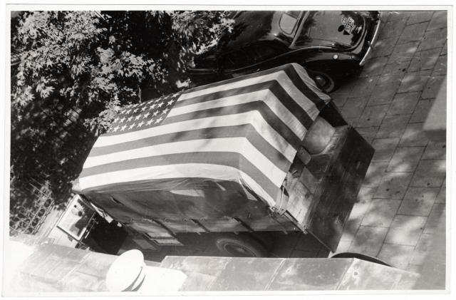 Amerikai lobogóval lefedett teherautó a nagykövetség udvarán