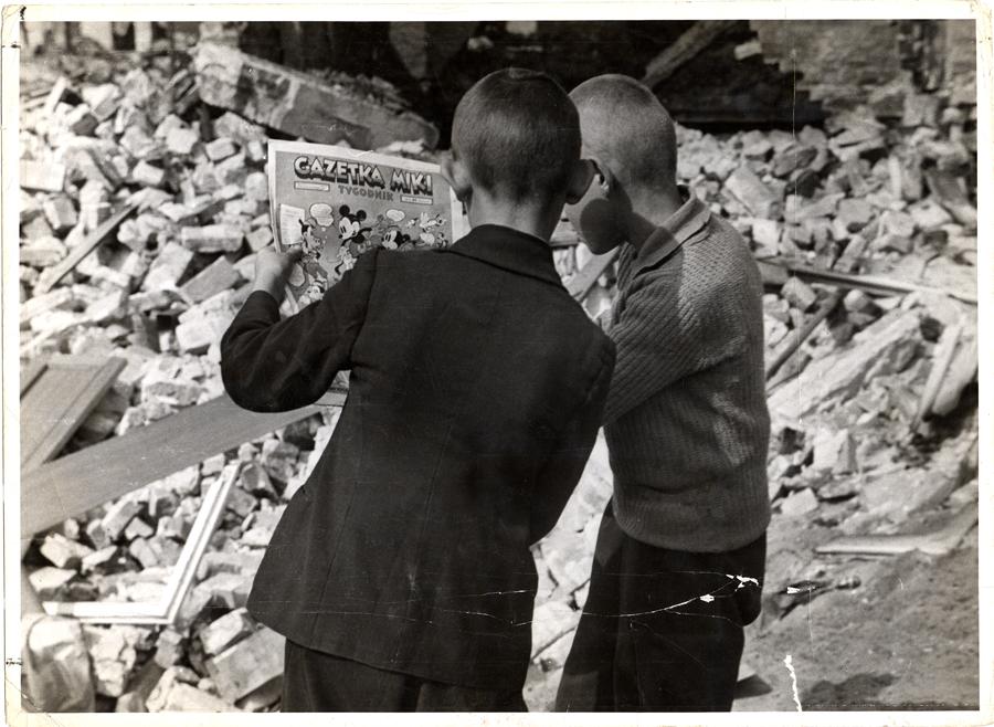 Gyerekek a Miki Egér magazint olvassák a romok között