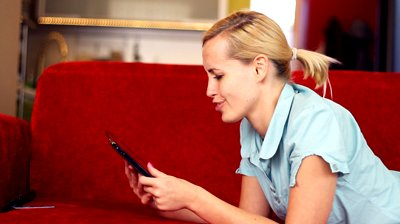 stock-footage-happy-attractive-woman-chatting-on-tablet-computer-on-sofa.jpg
