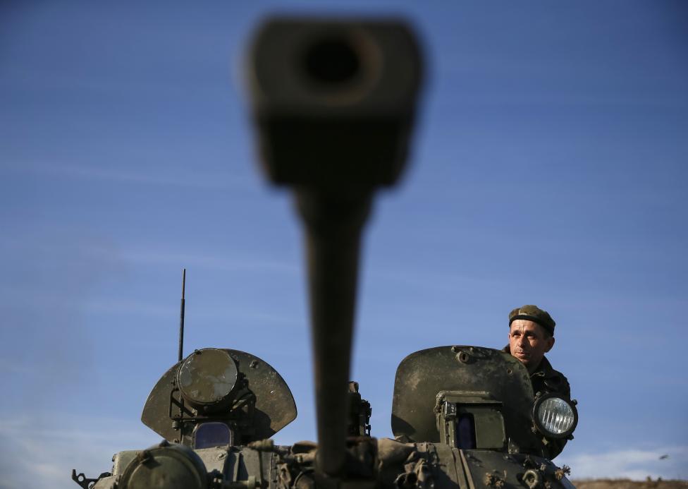 Ukrán katona szemléli a horizontot egy tank tetejéről Kurakovóban, Donyeck mellett (f.: Reuters)