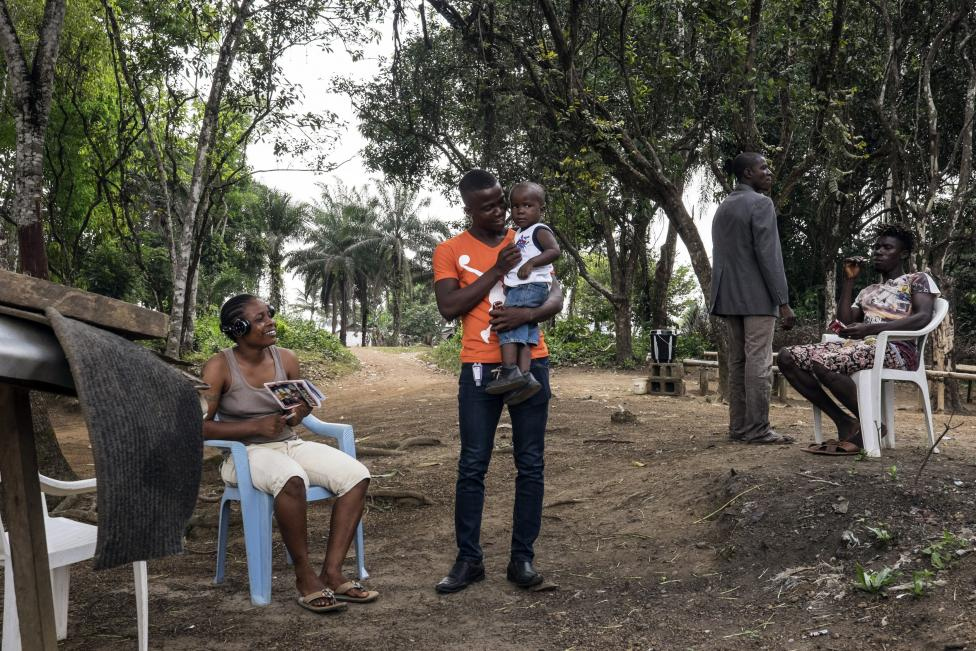 Egy ebolát túlélő férfi tartja első alkalommal a karjaiban gyermekét Libériában, miután véget ért számára a több hónapos karantén megfigyelés időszaka (f.: Reuters)