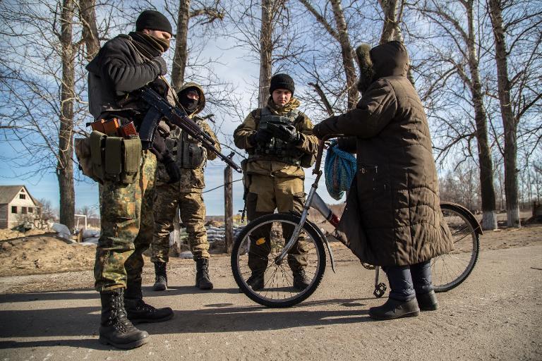 Katonák ellenőrzik egy biciklis helyi lakos papírjait Luganszk megyében (f.: Reuters)