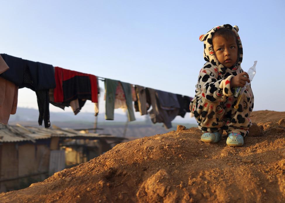 Kisgyermek eszik a kínai határhoz közeli menekülttáborban, Mianmarban (f.: Reuters)