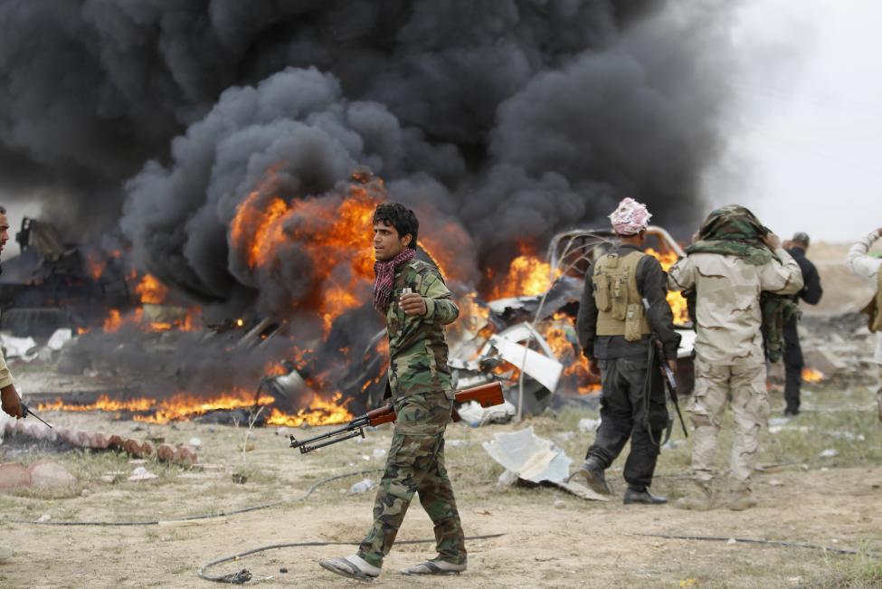 Síita milicisták állnak egy az Iszlám Állam öngyilkos merénylői által vezetett és önmagukkal együtt felrobbantott jármű előtt az iraki Tikrit városánál. Az iraki hadsereg és a milicisták a héten visszafoglalták a várost, stratégiai vereséget mérve a radikális iszlamista csoportra. (f.: Reuters)