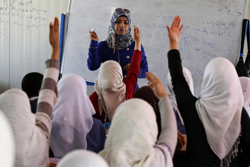 Lányok jelentkeznek egy szíriai menekülttáborban felépített ideiglenes iskolában (f.: Reuters)