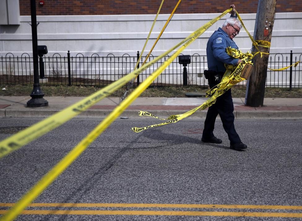 Rendőrtiszt bújik át a biztonsági szalag alatt Fergusonban, ahol a napokban 2 rendőrt is meglőttek a helyi tüntetések alatt.  (f.: Reuters)