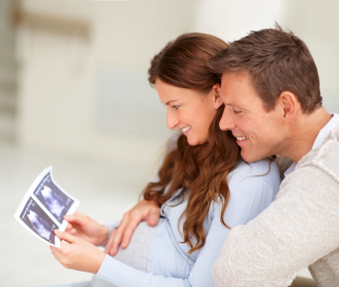 Pregnant-couple-looking-at-ultrasound-scan-pic.jpg