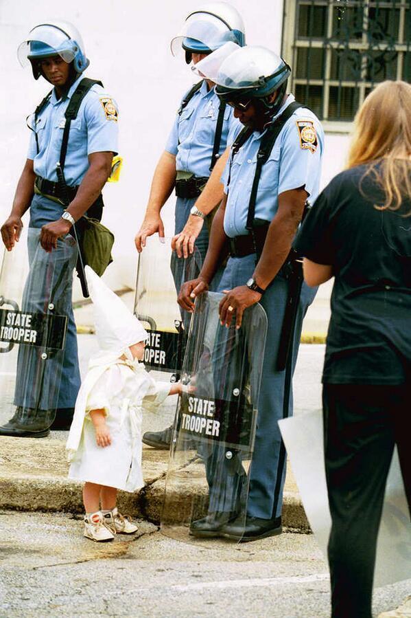 fehér kisfiú megérinti egy fekete rendőrtiszt pajzsát a ku klux klán felvonulásán.jpg