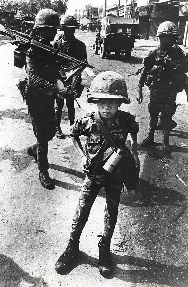 little-tiger-a-child-soldier-rumored-to-have-killed-his-mother-and-his-teacher-stands-for-a-photograph-in-1968.jpg