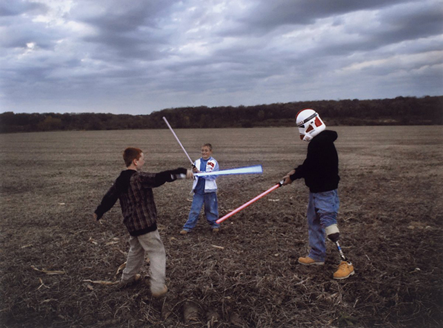 raymond-hubbard-an-iraq-war-veteran-with-a-prosthetic-leg-puts-on-a-star-wars-storm-troopers-helmet-and-engages-his-sons-in-a-light-saber-battle-in-2007-his-father-was-similarly-injured-in-vietnam.jpg