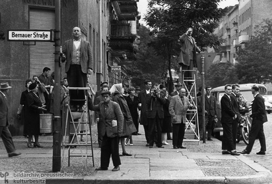 1961. Augusztus 13. Bernauer Strasse. Nyugat-Berliniek figyelik az épülő falat..jpg