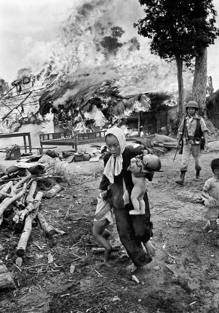 1963. Civilek menekülnek égő falujukból, mögöttük dél-vietnami katona..jpg