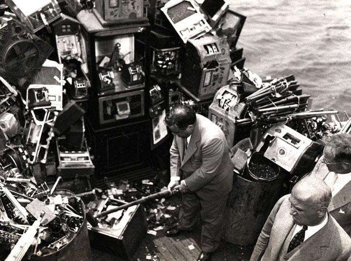 1934. Fiorello LaGuardia new york-i polgármester pénznyerő automatákat tör össze és dob az öböl vizébe..jpg