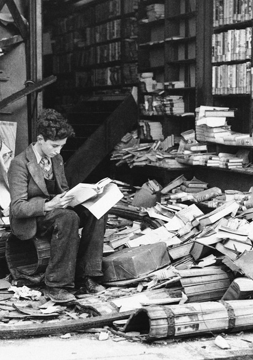 1940. London. Egy fiatalember a lebombázott könyvesbolt romjai közt olvas..jpg