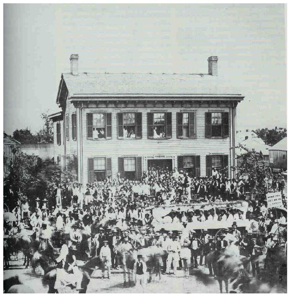 1860. Abraham Lincoln háza Springfieldben, körülvéve támogatóival. Lincoln a magas, szakállas férfi, mellényben a tornác előterében..jpg