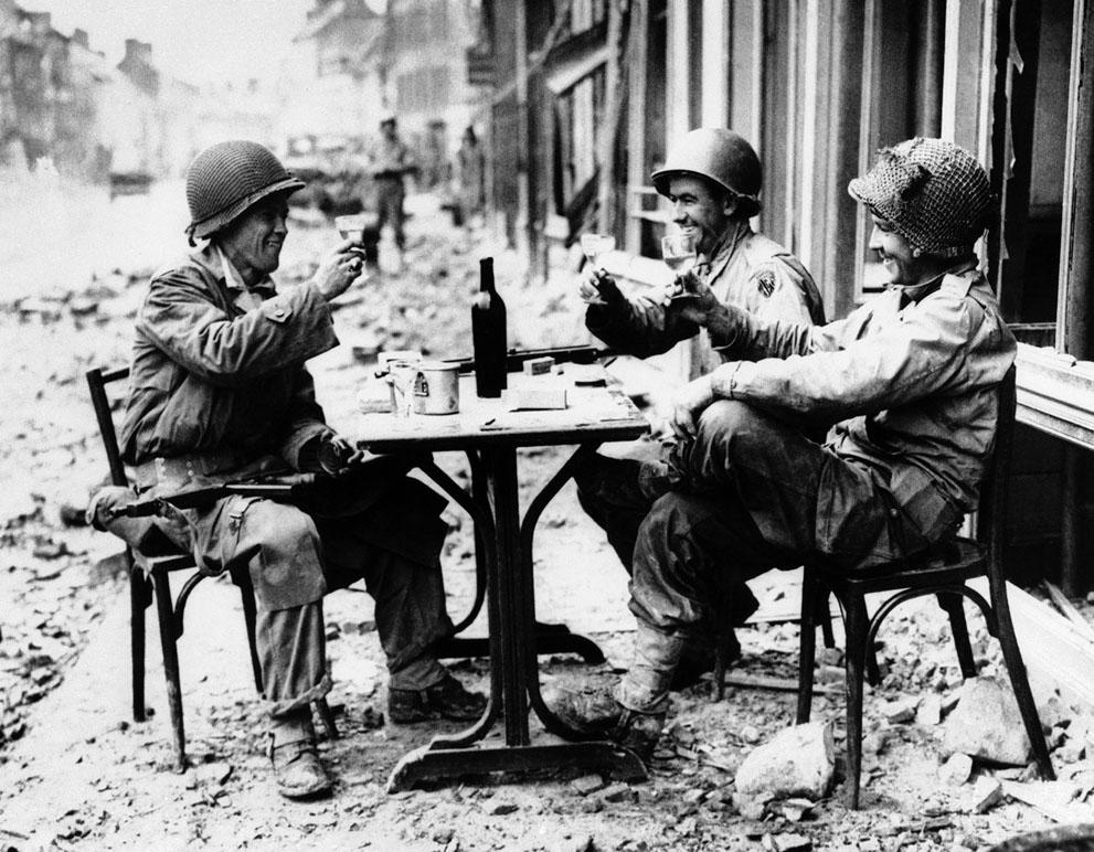 1944. Három amerikai katona iszik, egy ostrom után elfoglalt francia városka kocsmája előtt..jpg
