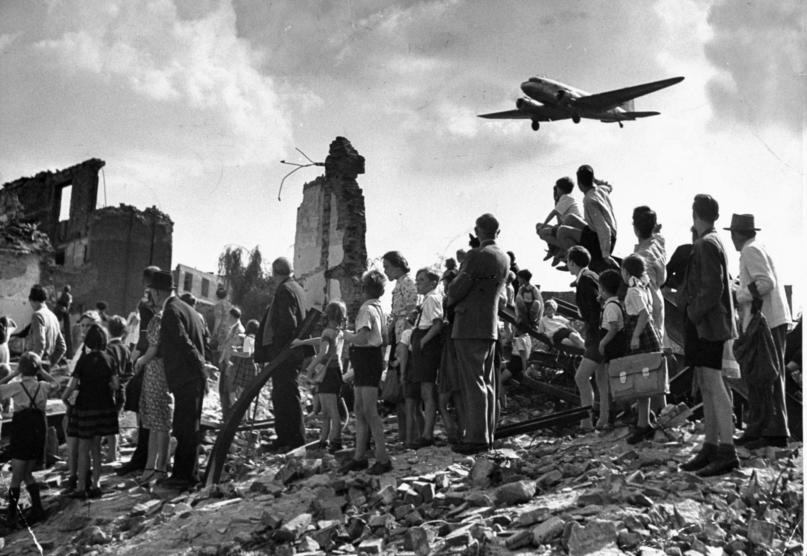 1948. Nyugat-Berliniek nézik a légihídon át ellátmányt szállító C47-es repülőt, ami leszállni készül a Tempelhof reptéren..jpg