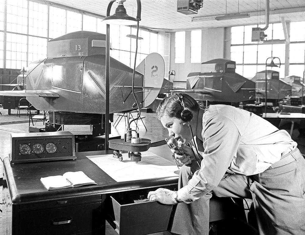 1943. Epson repülőgépszimulátorral dolgozó repülésirányító adje az utasítást a szimulátorban ülő pilótajelölteknek..jpg