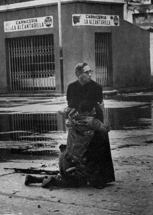 1962. Luis Padilla atya vonszolja el az utcáról a mesterlövész által halálosan megsebesített katonát Puerto Cabello-ban Venezuelában..jpg