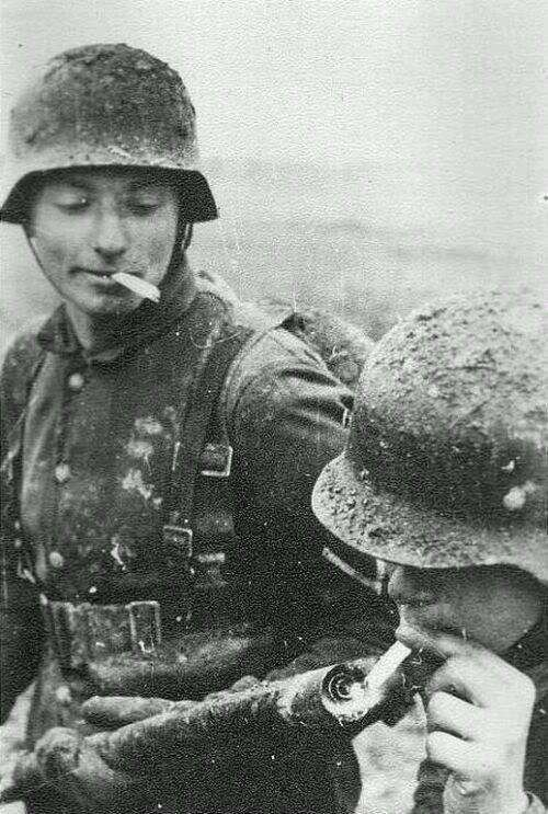 1940. Német katona lángszóróról gyújt cigarettára..jpg