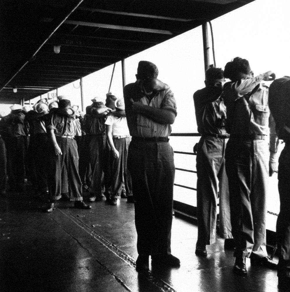 1946. július. A Bikini atollon robbanó nuklearis bomba villanása elől szemület eltakaró amerikai tengerézek..jpg