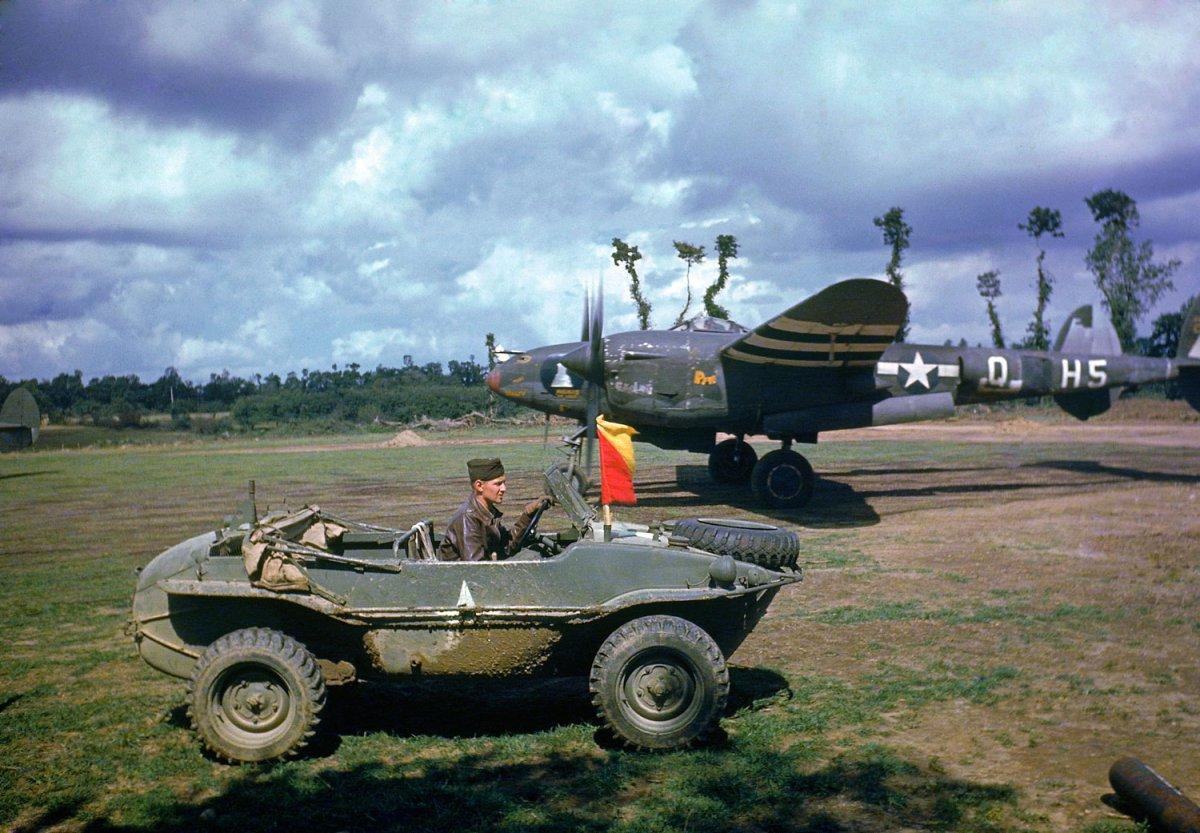 1944. P-38 repülőgép egy francia reptéren. Előtérben egy amerikai katona zsákmányolt német kétéltű terepjáróban..jpg