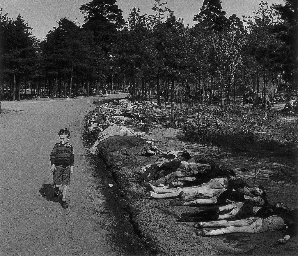 1945. Német fiú a felszabadított bergen-belseni koncentrációs táborban a kivégzettek sorfala előtt, rezzenéstelenm arccal sétál. A háttérben a fák között is hullahegyek..jpg
