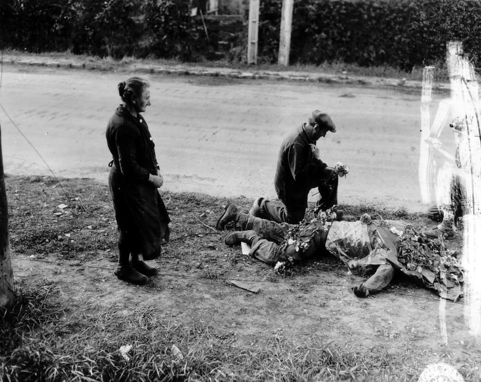 1944. Carentan Franciaország. Civilek fejezik ki tiszteletüket egy elesett amerikai katonának..jpg