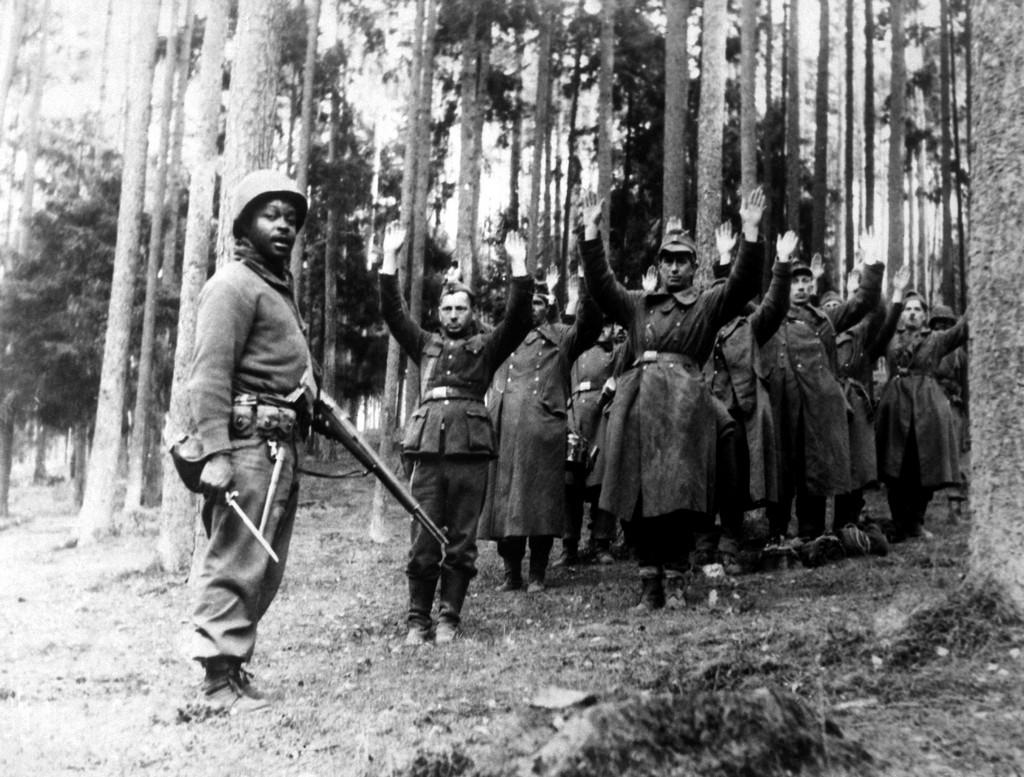 1945. Afroamerikai katona felügyel a magukat megadó német katonákra..jpg