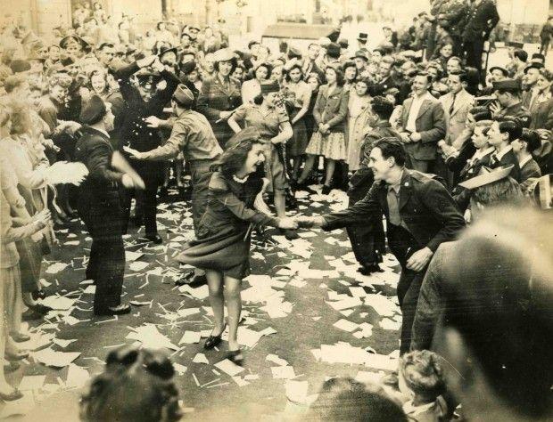 1945. London, Piccadilly. Katonák, rendőrök és civilek táncolva ünneplik a háború befejezését..jpg