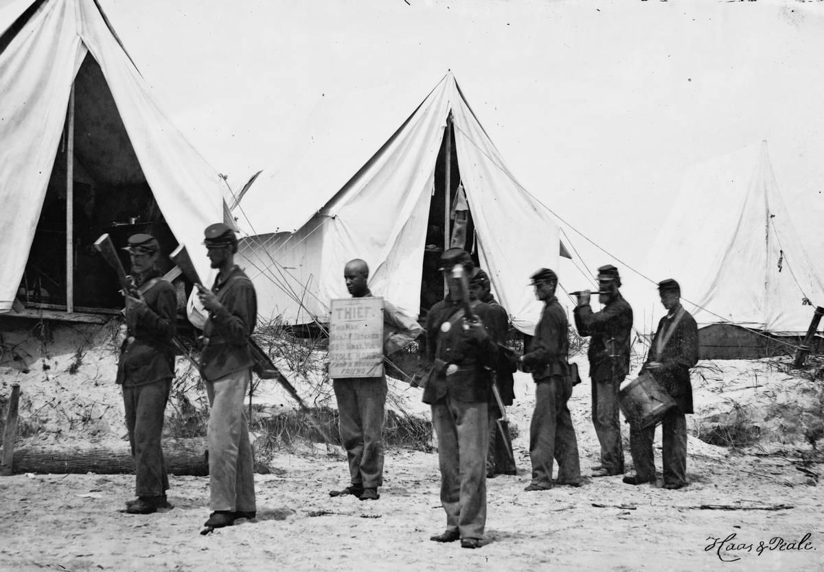 1863. Északi katona, nyakában táblával TOLVAJ! Pénzt lopott sebesült társától..jpg