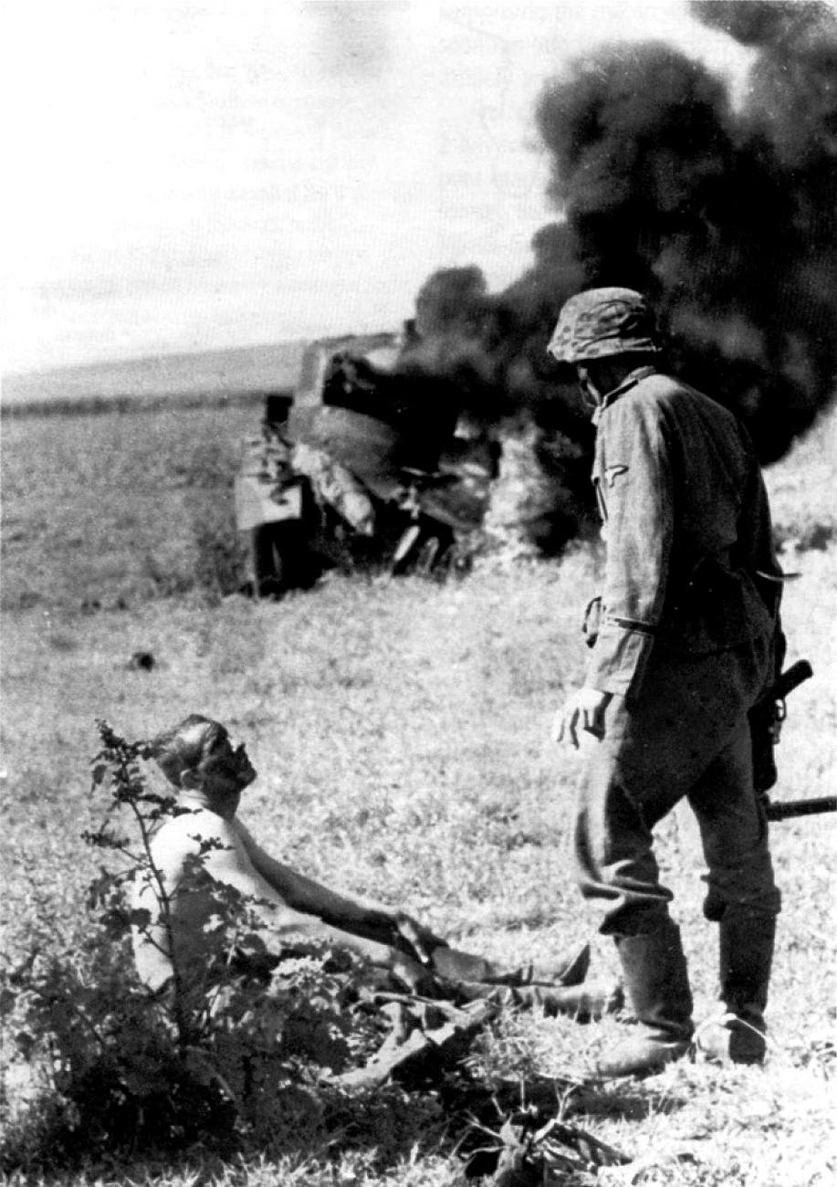 1941. Barbarossa hadművelet során egy német SS katona hallgatja az egyetlen túlélőt egy kilőtt szovjet tankból..jpg