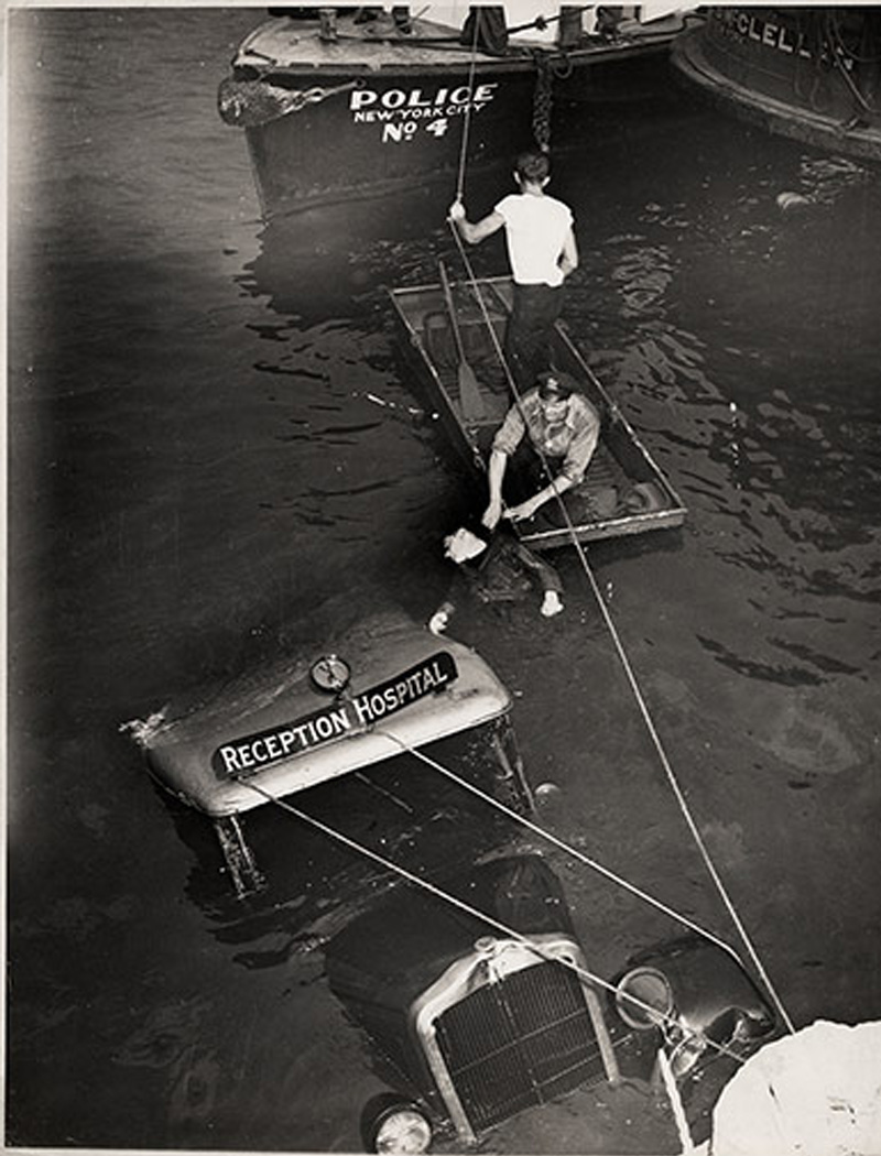 1943. Egy balesetet szenvedett mentőautó-sofőr holttestének kiemelése az East Riverből, New York..jpg