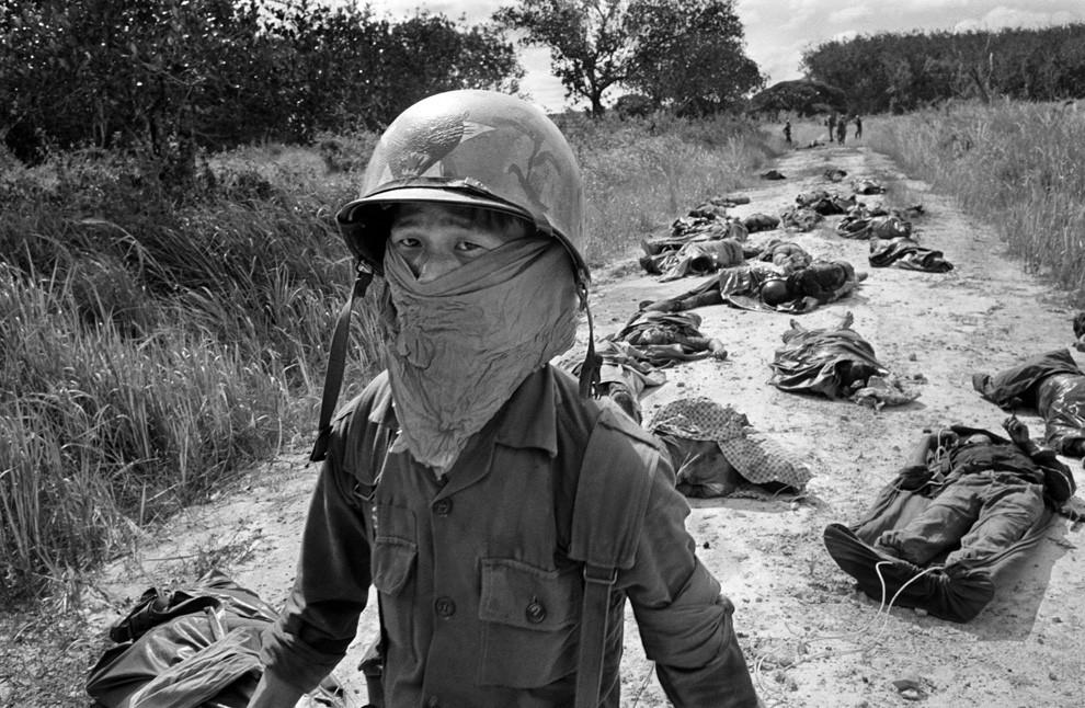 1965. Vietnami fiú több napja halott amerikai katonák mellett halad el..jpg