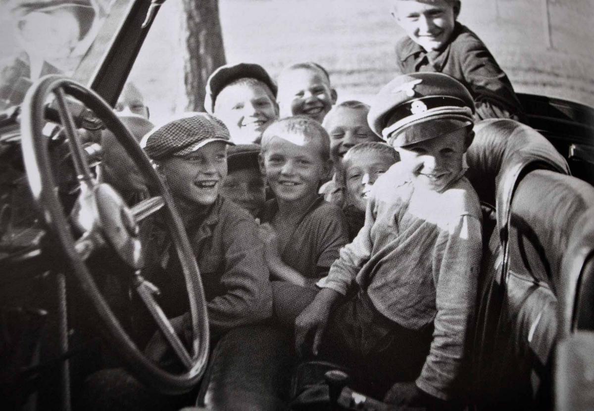 1941. Novinki. Szovjet gyerekek játszanak Himmler sapkájában és autójában..jpg