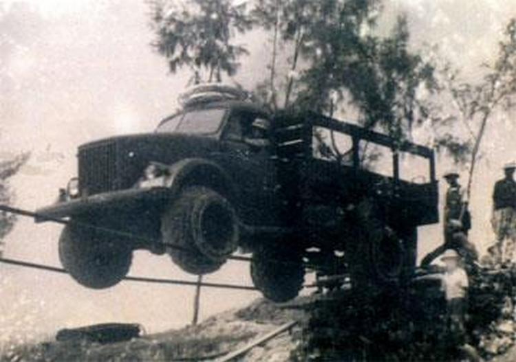 1965. Vietkong erők ideiglenes kábelhídon kelnek át egy gyors sodrású hegyi folyó felett..jpg