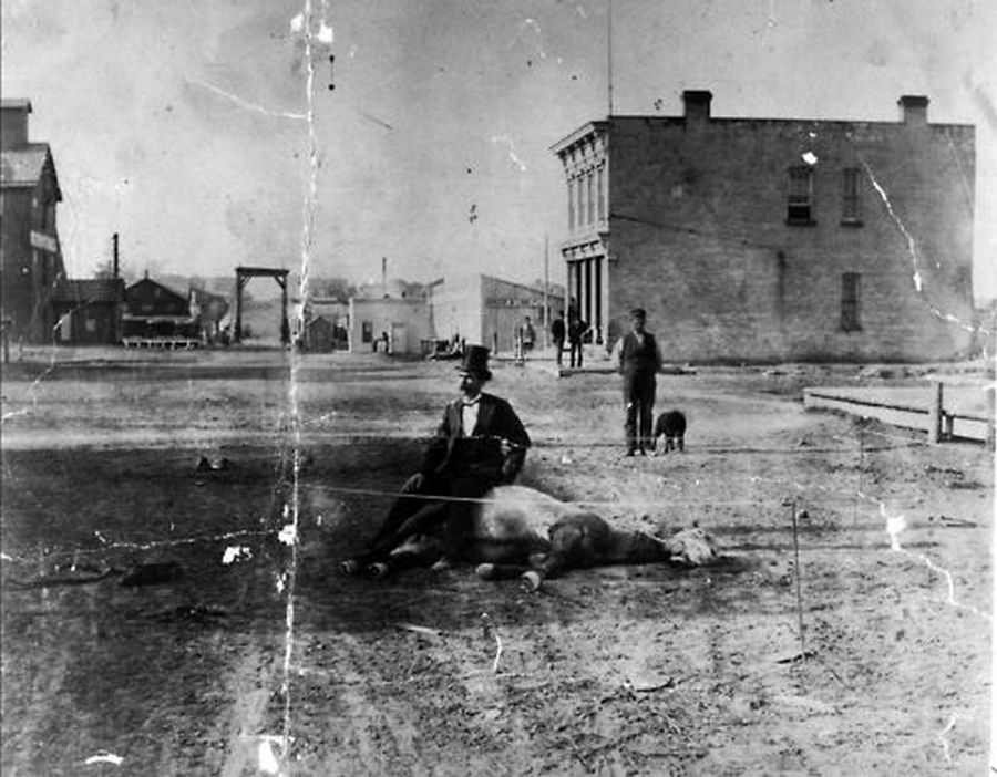 1880. Sheboygan, Wisconsin. Halott lován ül gazdája..jpg