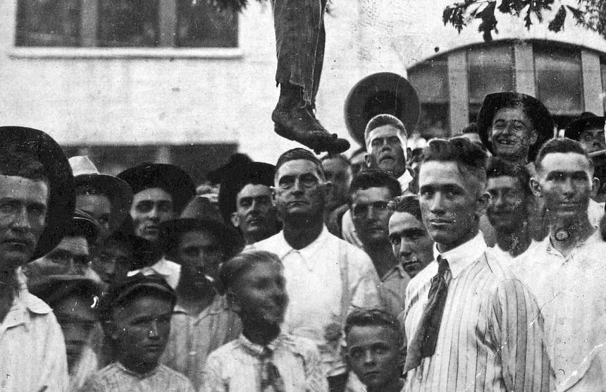1920. USA, Texas. Egy meglincselt, 16 éves fekete fiú akasztott holtteste körül fényképeszkedő helybéliek..jpg