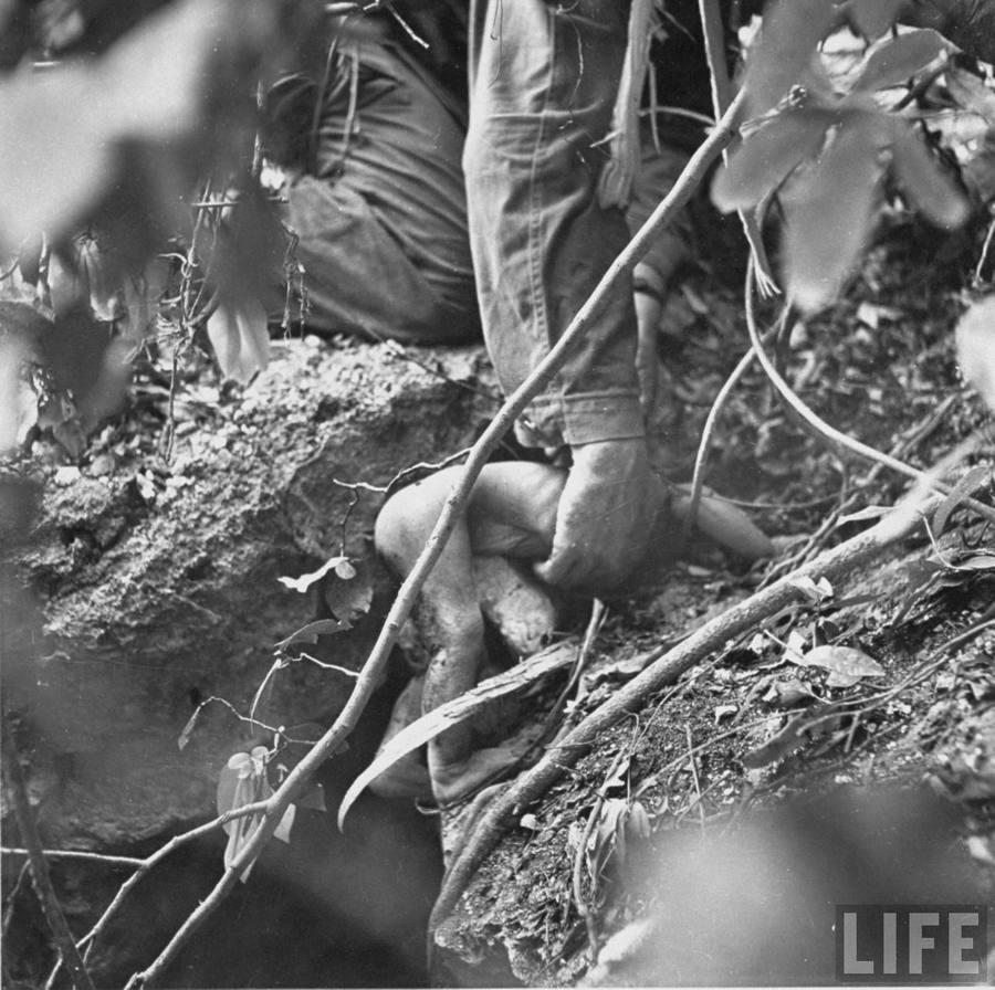 1944. Saipan, Csendes-óceáni hadszintér. Amerikai tengerészgyalogos emeli ki egy beomlott óvóhelyről egy életben lévő benszülött kisbaba testét..jpg