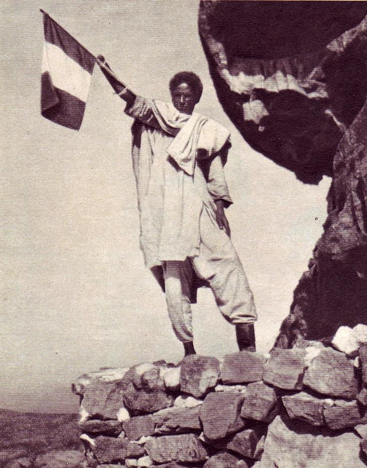 1935. Csonkolt etióp katona olasz zászlót lenget. A második olasz abesszín háborúban azokat az abesszínokat, akik az olaszok mellé álltak, jobb kezük és bal lábfejük levágásával bűntették..jpg