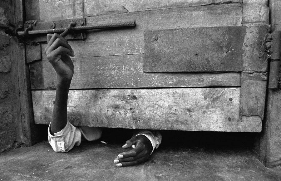 1994. Egy férfi próbálja cellája ajtaját kívülről kinyitni a ruandai népírtás idején Kigaliban..jpg