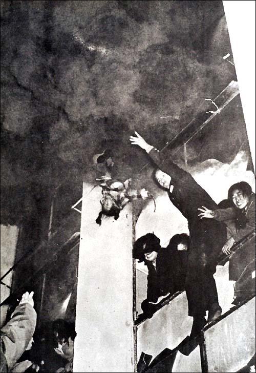 1972. Szöul, Dél-Korea. Egy hatéves kislányt dobnak ki az égő Civic Hall épületéből. A tűzben hatvanan haltak meg, a kislány megmenekült, a lent álló tűzoltók elkapták..jpg