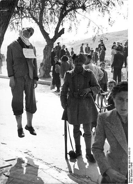 1943. Egy görög katona áll egy akasztott civil mellett a német megszállás idején..jpg