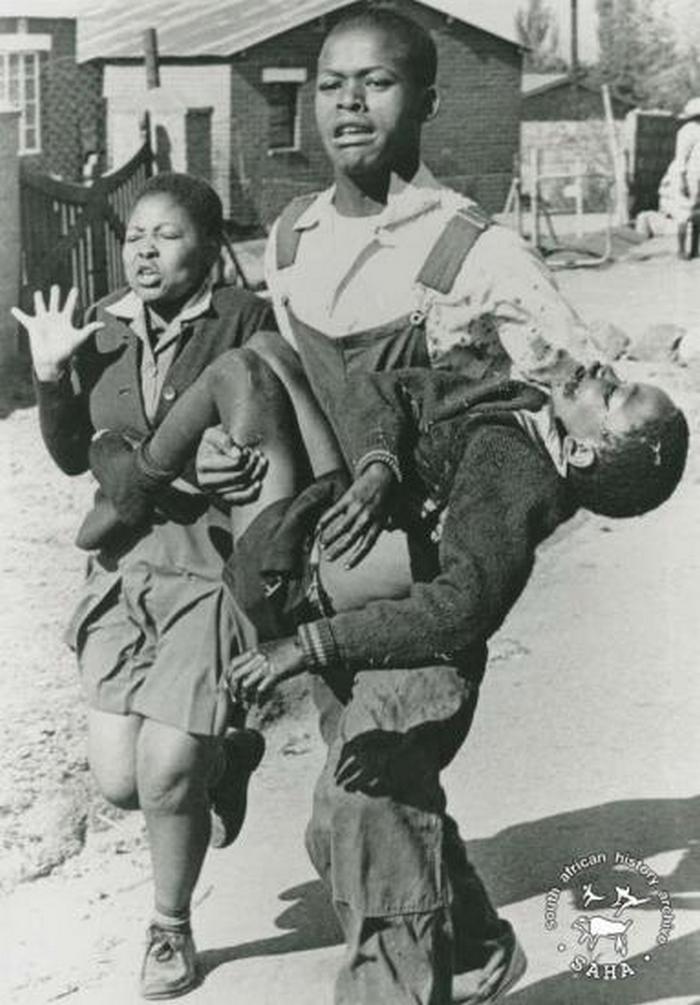 1976. A 13 éves Hector Pieterson-t ok nélkül lőtte le az apartheid rendszer rendőrsége Dél-Afrikában. Nővére és barátja rohannak vele segítségért..jpg