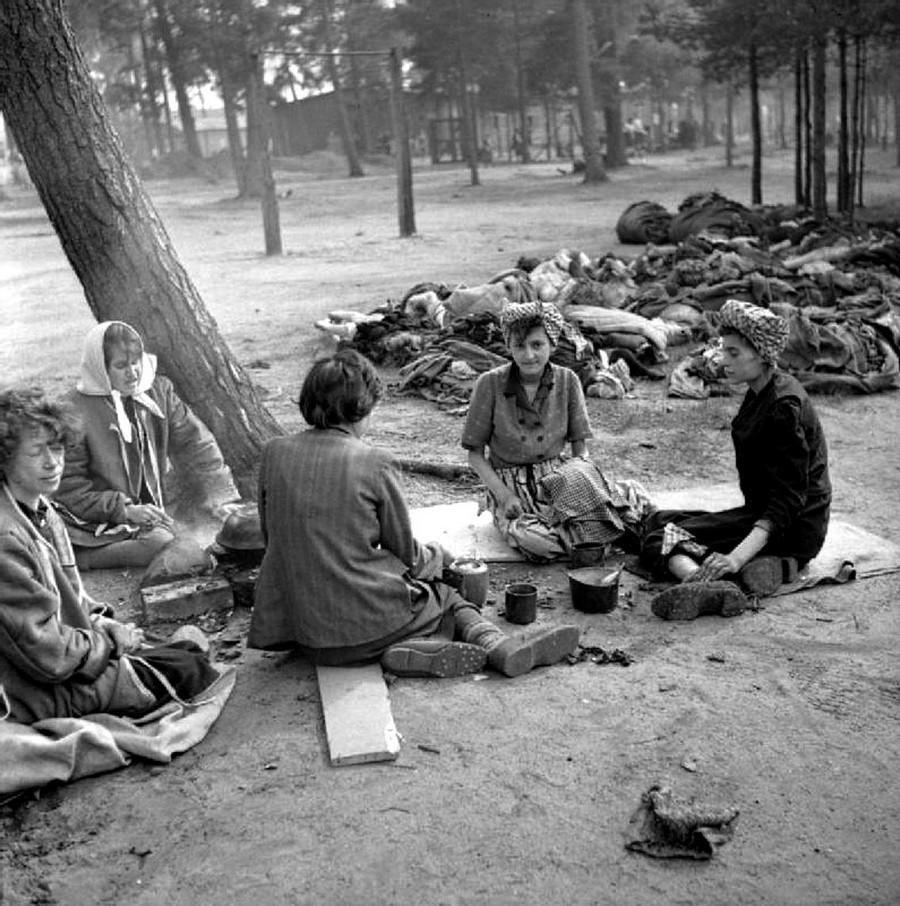 1945. április 18. A frissen felszabadított bergen-belseni tábor lakói ebédet főznek a halottak közvetlen közelében..jpg