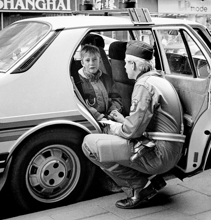 1986. Svéd rendőr vígasztalja a randőrautóban síró gyereket, aki belesetet okozott gördeszkájával..jpg