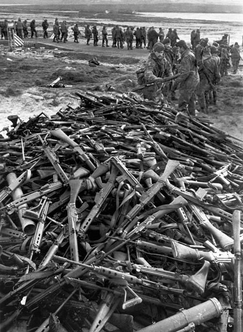 1982. Argentín hadifoglyok adják le fegyvereiket a Royal Marines katonáinak Port Stanley-ben a Falklandi háború végén..jpg