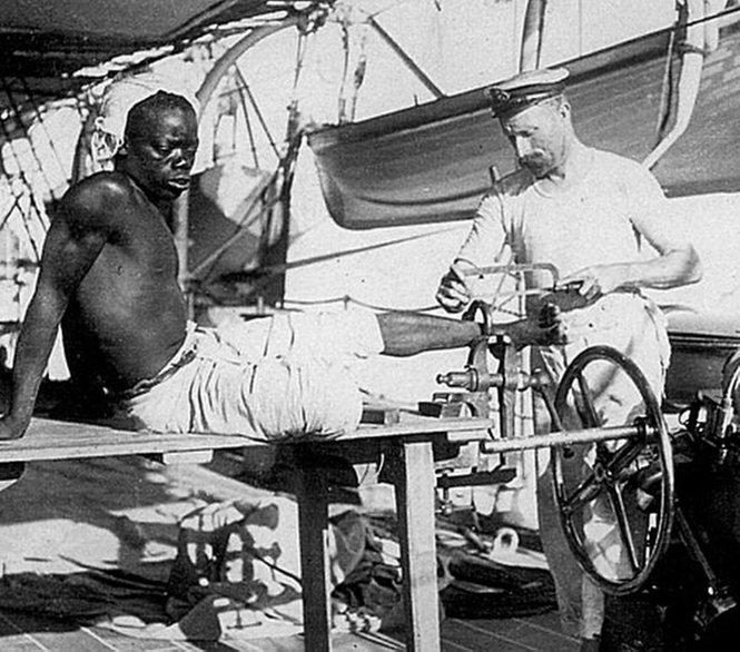1890 körül. Brit tengerész vágja le egy rabszolga bilincseit..jpg