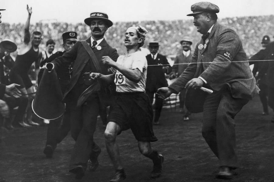 1908. Dorando Pietri az 1908-as olimpia maratonjának befutójában. Első lett, de később diszkvalifikálták, mert az utolsó métereken segítettek neki..jpg