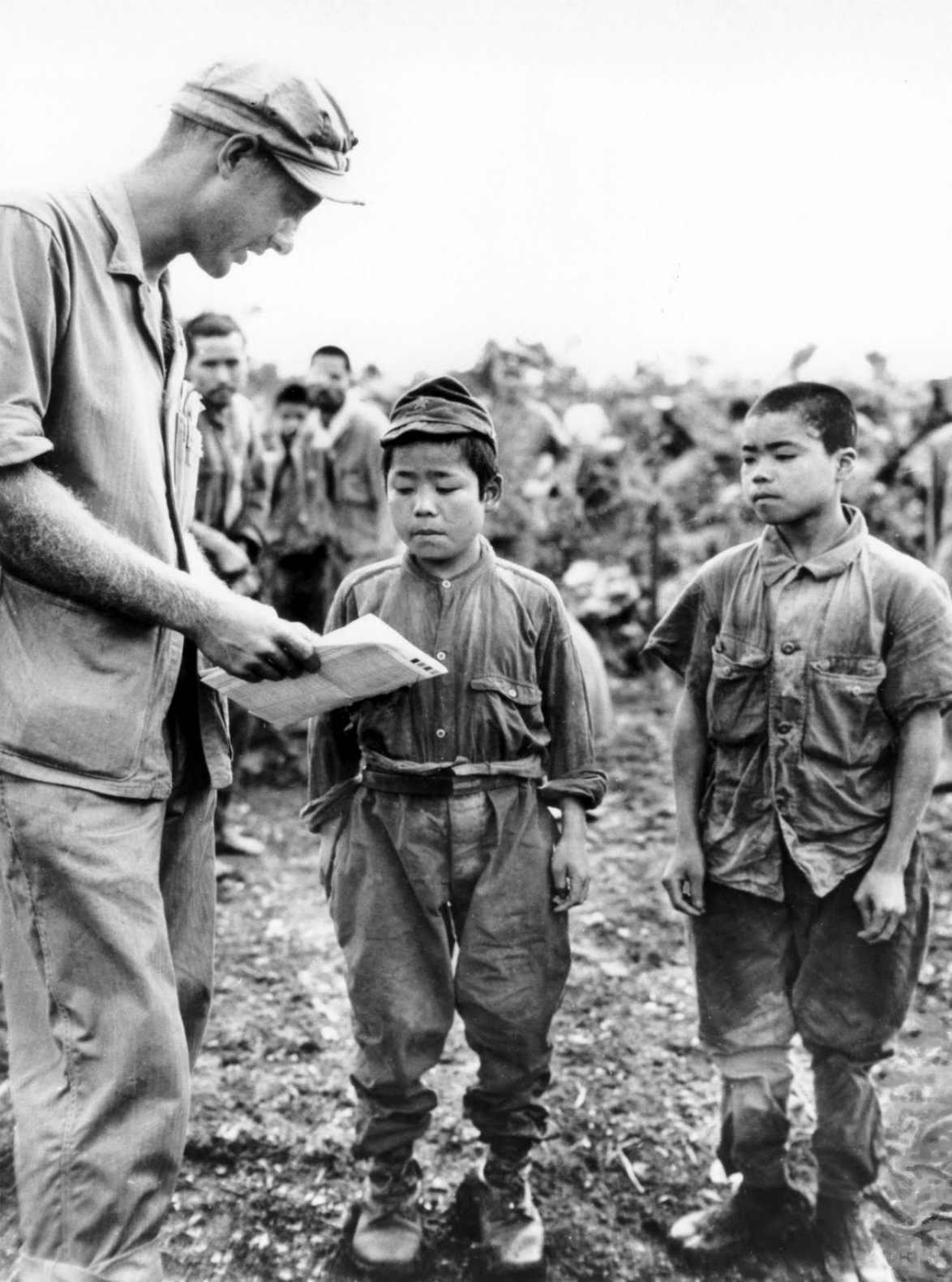 1945. június. U.S. Marine 1st Lt. Hart H. Spiegal própál kommunikálni két japán gyerekkatonával Okinawán..jpg